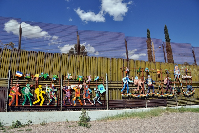 A painted metal mural attached to the Mexican side of the US border wall in the city of Heroica Nogales, Sonora. Photo by Jonathan McIntosh, Creative Commons License