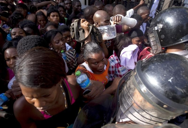 Haitians face police while waiting outside the Ministry of Interior and Police to register in Santo Domingo, June 16, 2015. © 2015 Reuters