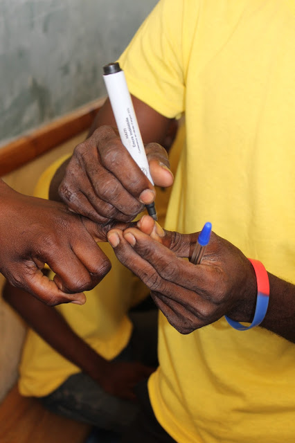A finger being marked to indicate a completed vote.